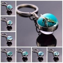 Blauw zeeleven - ronde dubbelzijdige glazen sleutelhanger - schildpad / dolfijn / schelpen